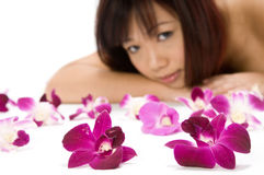 Tropical Beauty. A young Asian woman lying on the floor with purple orchid flowers Stock Photography