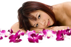 Tropical Beauty. A young Asian woman lying on the floor with purple orchid flowers Royalty Free Stock Photography