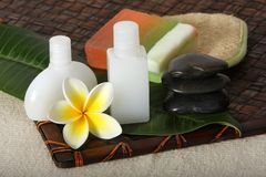 Tropical Beauty Day Spa. Close up of hot massage river stones with yellow and white frangiapani flower and leaf with beauty day spa products - soap, lotions and Stock Images