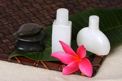 Tropical Beauty Day Spa Products. Close of pink frangiapani / plumeria flower with day spa beauty products on leaf and woven bamboo mat Stock Photo