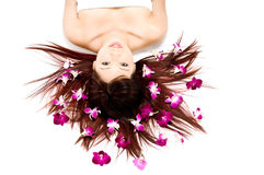 Tropical Beauty on White. A young Asian woman lying on the floor with purple orchid flowers Stock Image