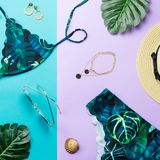Tropical bikini swimsuit, beach fashion. Traveler woman accessories flat lay with swimwear, palm leaves. Tropical bikini swimsuit and woman accessories, beach Royalty Free Stock Photography