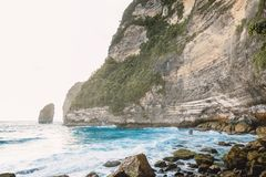 Tropical blue ocean with waves and rocky cliff in Bali. Rocks and sea. Tropical blue ocean with waves and rocky cliff in Bali. Rocks and tropical sea Stock Images