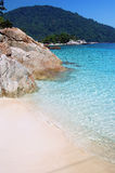 Tropical blue sea with stone and sand royalty free stock photography