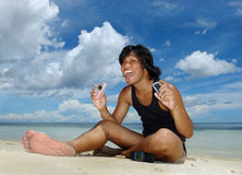 Tropical boy with 3 cell-phones. Asian young adult male on a tropical exotic beach using three cell-phones. Concept of information overload and extreme stock image