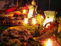 Tropical Buffet Table. Candlelit tropical buffet table filled with delicious food Stock Photo