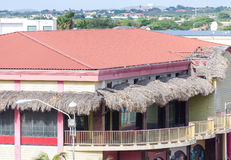 Tropical Building with Red Tile Roof and Thatched Awnings. A yellow tropical building with thatched awnings over balcony and a red tile roof Stock Photos