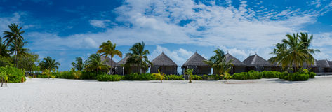 Tropical bungalos panorama view at resort with white sand and palm trees at Maldives Stock Photo