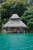 Tropical bungalow with thatched roof over water Stock Images