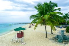 Tropical Caribbean island white sand summer beach scene. Tropical Caribbean island beach scene. Life guard tower, coconut palm trees, white sand stock images