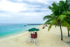 Tropical Caribbean island white sand summer beach scene. Tropical Caribbean island beach scene. Life guard tower, coconut palm trees, white sand stock photo