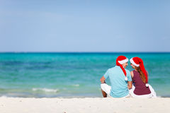 Tropical Christmas. Back view of young romantic couple in red Santa hats sitting on beach and looking to each other Stock Photos