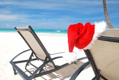 Tropical christmas. Santa's hat and chaise lounge on the beach. Blue halo around hat is only on preview stock photo
