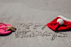 Tropical Christmas at the beach, with happy holidays written in stock photos