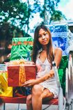 Tropical Christmas concept. Young woman in Santa Claus sledge with shiny colorful gifts Stock Image