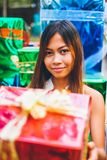 Tropical Christmas concept. Young woman in Santa Claus sledge with shiny colorful gifts Stock Images