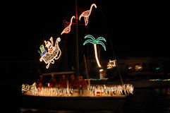 Tropical Christmas lights. A sailboat traveling at night with christmas lights of santa, flamingos and a palm tree in its sail.(some motion blur royalty free stock images