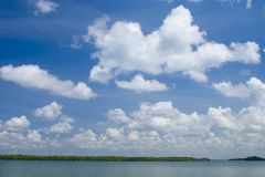 Tropical Clouds. A blue, clouded sky hovers over tropical mangrove islands and open water stock images