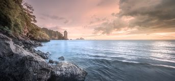 Tropical coast, jungle and cliff of Thailand beach. Beautiful sunset and dramatic clouds over the tropical island, Thailand. Vacation and background concept stock photography