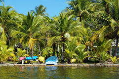 Tropical coast with kayaks and small boat. Tropical coast with coconut palm trees and colorful kayaks with a small boat awaiting tourists, Caribbean, Carenero Stock Image