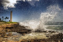 Tropical coastal storm. Stormy weather with large wave crashing into the leeward coast of Oahu Hawaii. Barber's Point Lighthouse in the background Stock Photos