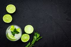Tropical cocktail. Beverage which women likes. Glass of mojito with slices of lime, mint, ice cubes on black background stock photos