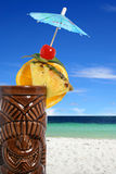 Tropical cocktail drink at the beach. A tropical cocktail drink garnished with fruits, umbrella and served in a tiki style mug on a tropical beach stock image