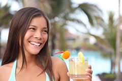 Tropical cocktail woman at summer pool resort. Woman having drink at tropical resort. Beautiful smiling mixed race caucasian / chinese young woman model Royalty Free Stock Photo