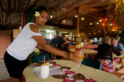 Tropical cocktails in Aitutaki Lagoon Cook Islands. AITUTAKI - SEP 19:Cook Islander woman serve cocktails on Sep 17 2013.Some of the best resorts in the pacific Royalty Free Stock Photos