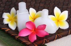 Tropical Day Spa Beauty Products. Close of pink, yellow and white frangiapani / plumeria flower with day spa beauty products on leaf and woven bamboo matt Stock Images