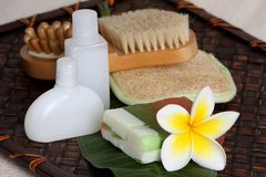 Tropical Day Spa Beauty Products. Close of yellow and white frangiapani / plumeria flower with day spa beauty products on leaf and woven bamboo mat Royalty Free Stock Photography