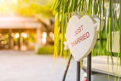 Just married sign formed into a heart shape with blurred background. Tropical destination honeymoon background concept stock photo
