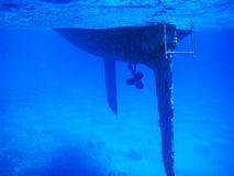 Tropical diving picture of a hull from a sailing vessel. Clear blue water. Under water sailboat with algae on the anti fauling paint. Rudder and propeller Royalty Free Stock Images