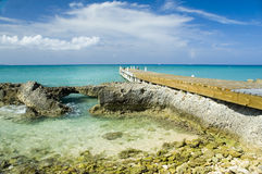 Tropical dock. A wooden dock juts into the caribbean sea from this tropical island Stock Photo