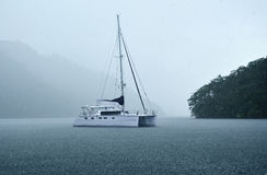 Tropical downpour. Sailig catamaran at ancor in Scotland bay under tropical downpour. Trinidad Stock Images