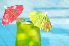 Tropical drink. Green tropical cocktail with pool background Stock Photos