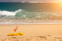 Tropical Drink and Flower Lei on Beach Shoreline Royalty Free Stock Image