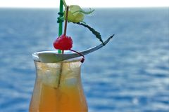Tropical drink with fruit and blue ocean background royalty free stock photo