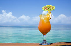 Tropical Drink Paradise. A refreshing drink, with an tropical paradise in the background Stock Photography