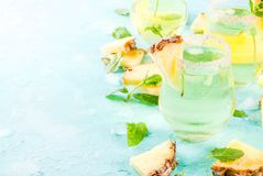Pineapple juice margarita. Tropical drink, Pineapple juice margarita cocktail with fresh mint, light blue background copy space Royalty Free Stock Photo