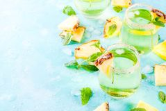 Pineapple juice margarita. Tropical drink, Pineapple juice margarita cocktail with fresh mint, light blue background copy space Stock Photos