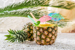 Tropical drink in pineapple on sandy beach. On bright background royalty free stock photography