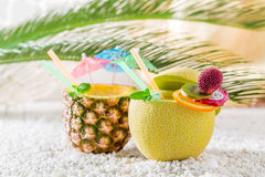 Tropical drinks in fresh fruits on sandy beach Royalty Free Stock Image
