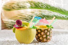 Tropical drinks in fresh fruits. On white pebbles Royalty Free Stock Photos