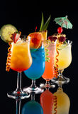 Tropical drinks - Most popular cocktails series. Tequila Sunrise, Blue Lagoon, Rum Runner, and Bahama Mama cocktails over black background on reflection surface stock image