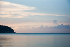 Tropical dusk in gentle blue and pink colors in Thailand, Koh Phangan. Silent sunset and still sea with some clouds and a rock in Thailand island Stock Images