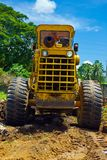 Tropical earthmover. Back view of a worn and rusted bulldozer or earthmover leveling residential tropical terrain with tree in background Royalty Free Stock Photo
