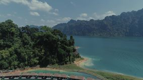 Tropical Thai jungle lake Cheo lan drone flight, wild mountains nature national park ship yacht, fishing boats. Tropical exotic green wild mountains sinset stock video