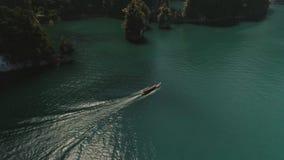 Tropical Thai jungle lake Cheo lan drone flight, wild mountains nature national park ship yacht. Tropical exotic green wild mountains sinset jungles drone 4k stock video