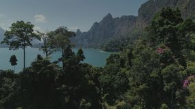 Tropical Thai jungle lake Cheo lan drone flight, wild mountains nature national park ship yacht rocks. Tropical exotic green wild mountains sinset jungles drone stock video footage